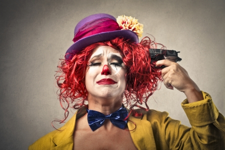 proble: clown shooting to herself Stock Photo