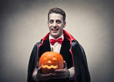 traditional parties: vampire holding a pumpkin