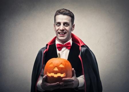 calabazas de halloween: vampiro sosteniendo una calabaza