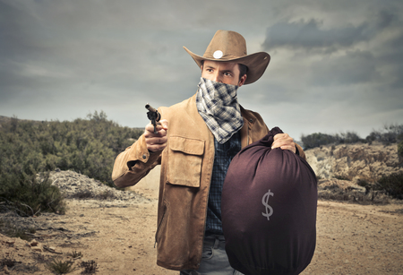 cowboy robber holding a gun and a bag full of money