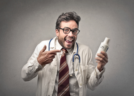 trickster: doctor smiling showing a medicine  Stock Photo
