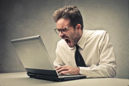 wanhopige zakenman werkt op zijn laptop