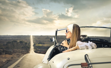 beautiful woman on a car looking at the landscape photo