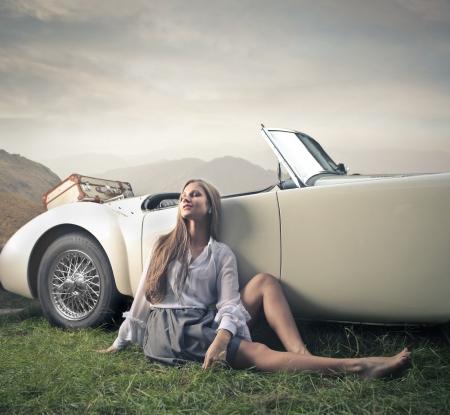 chillen: schöne Frau entspannt bei ihrem Auto