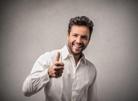 man glimlachend met duim omhoog Stockfoto