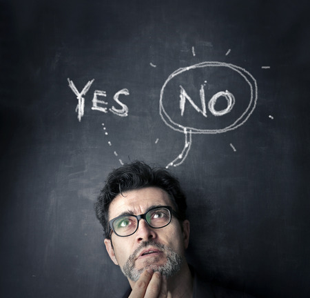 man with yes or no on black board Stock Photo
