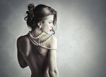 nude woman back: attractive woman with pearls jewellery Stock Photo