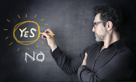 man with yes or no on a black board Stock Photo