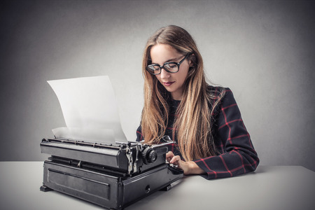Young journalist using a typewriter Stock Photo