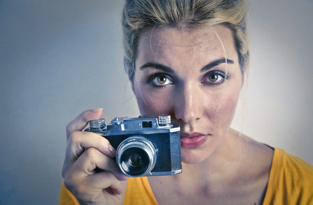 reflex: Blonde girl holding an old fashioned camera Stock Photo