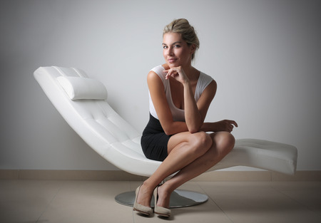 chaise longue: Classy businesswoman sitting on a white chaise longue