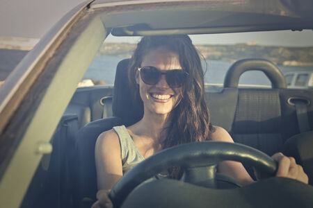 cabrio: Girl driving a car and smiling