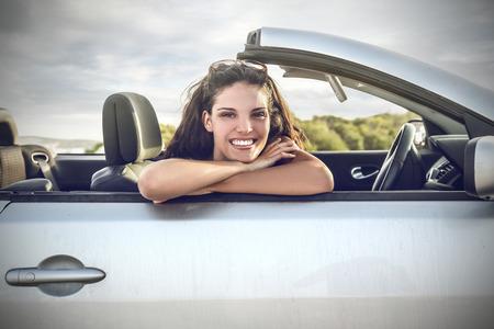 donna ricca: Ragazza sorridente in una macchina