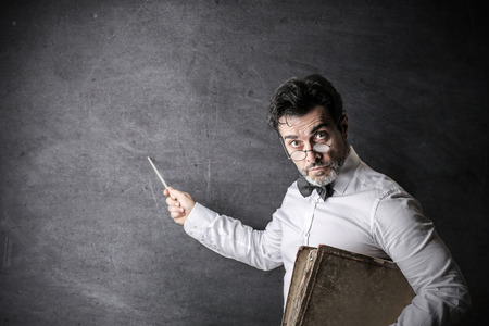 Serious teacher pointing out something on the blackboard