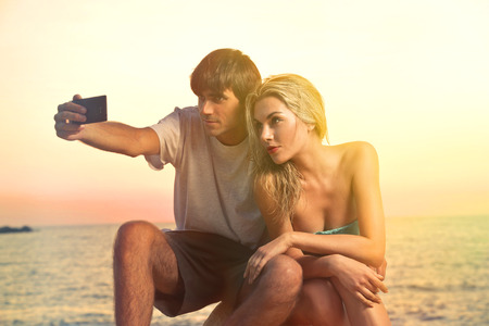 Couple at the seaside taking a selfie photo