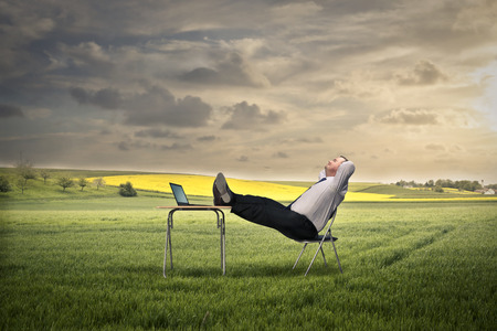 man sit: Businessman working in the green field  Stock Photo