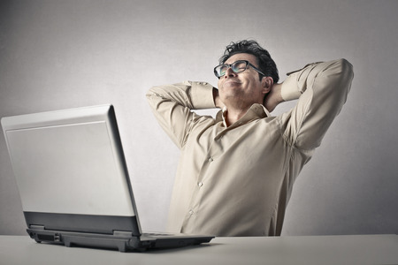 serenety: Man Stretching in front of his laptop  Stock Photo