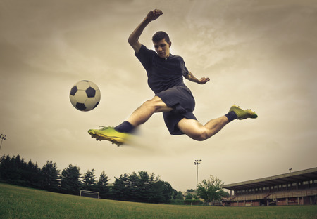 Young man kicking the ball
