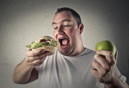 hombre comiendo: Apple y hamburguesa Foto de archivo