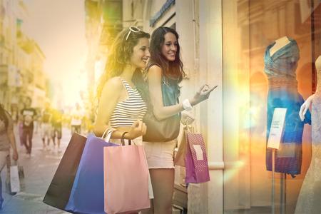 amigos: Dos amigos de compras ventana Foto de archivo