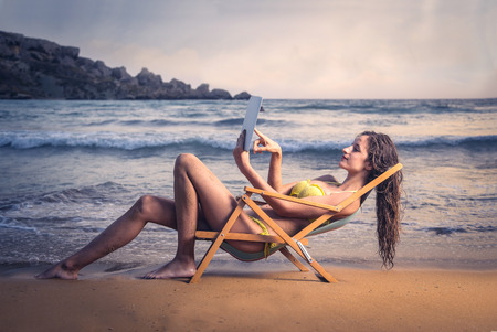 sunbed: Using a tablet at the beach Stock Photo