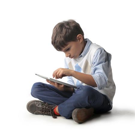 ni�os sentados: Ni�o utilizando una tableta Foto de archivo