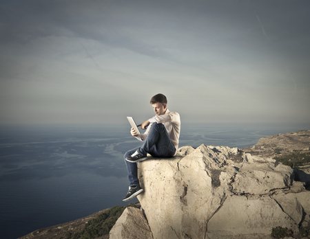 sitted: Using a tablet being sitted on the top of a rock