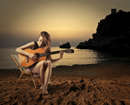 woman guitar: Playing guitar at the seaside Stock Photo