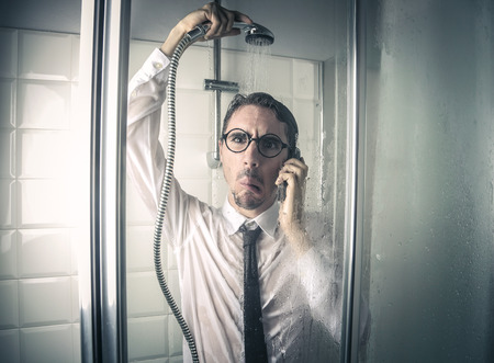 Confused businessman in a shower photo