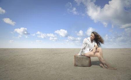mujer con maleta: Sentado en el medio del desierto