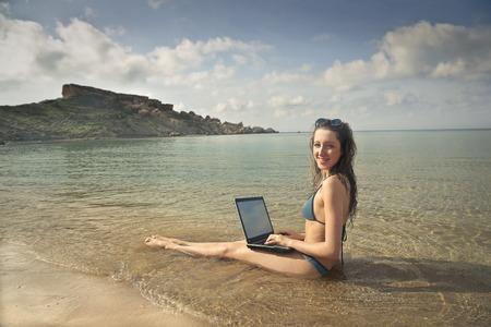 wet bikini: Working on a pc at the seaside Stock Photo