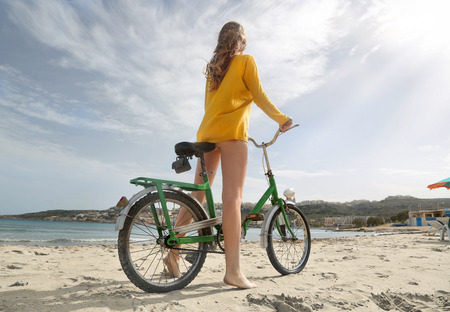 wellfare: A girl with her bike at the beach Stock Photo