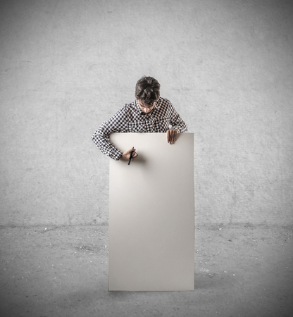 cartel: Man writing on a cardboard Stock Photo