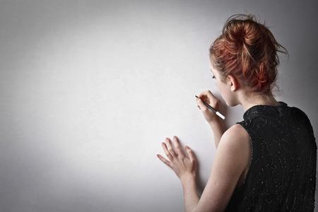 Woman writing on a wall Stock Photo