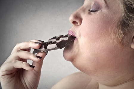 fat women: Eating chocolate Stock Photo
