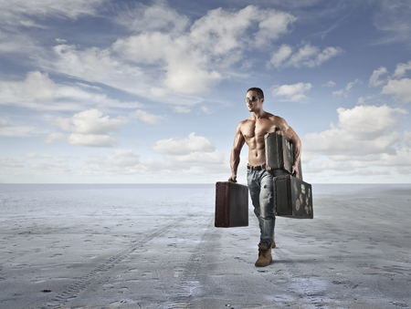 Hombre muscular que llevar maletas Foto de archivo - 36222677