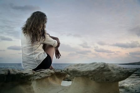 Lonely girl at the beach Stock Photo