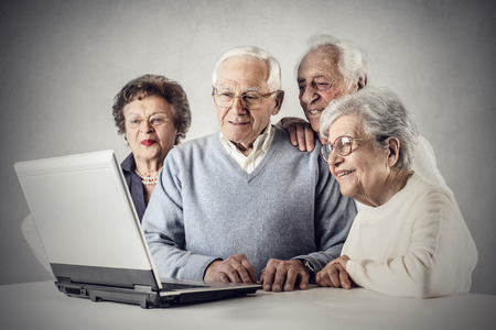 man working on computer: A group of elderly people using technology