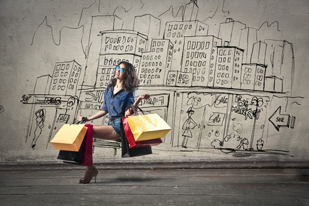 young woman sitting: Shopping in the city Stock Photo