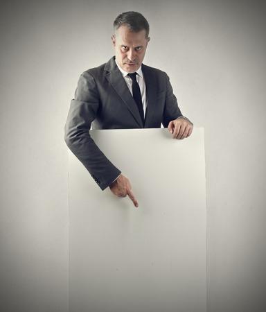 cartel: Businessman pointing at a blank cardboard