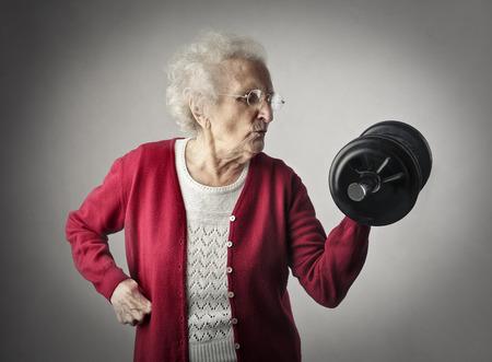 conceito: Mulher que levanta pesos idosos Banco de Imagens