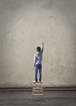 niños con lÁpices: Escritura Niño en una pared en blanco