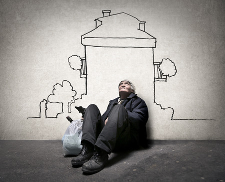 protection concept: Homeless man dreaming of a house