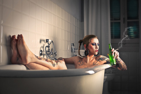Smoking and drinking in a bath tube Archivio Fotografico