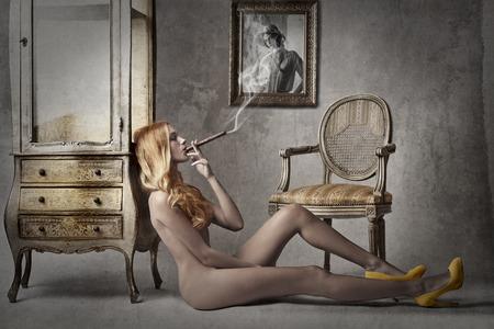 mujer desnuda sentada: Chica desnuda fumando un cigarro Foto de archivo