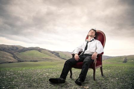 ビジネスマンの赤い椅子に座って