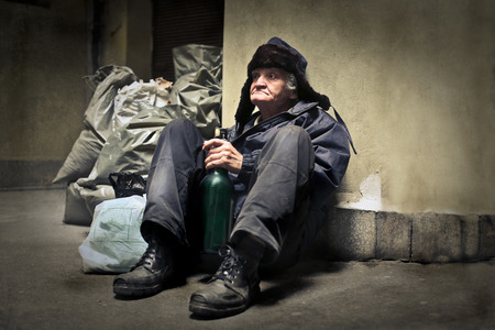 tramp: Homeless man sitting on the ground Stock Photo