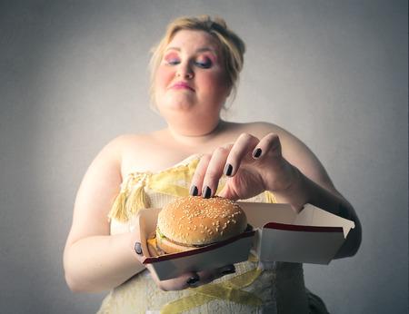 Chubby woman eating a hamburger