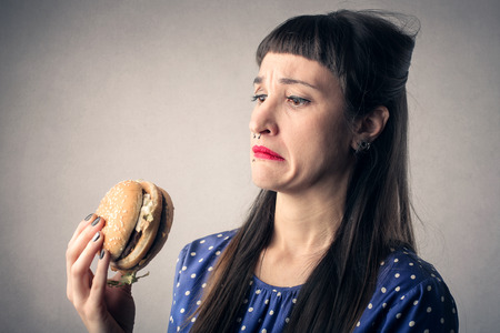 fast foods: Disgusted girl eating a hamburger