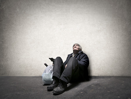 Homeless man sitting on the ground Foto de archivo